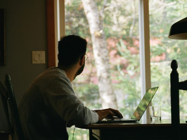 man in gray hoodie looking out a window while using a laptop at home