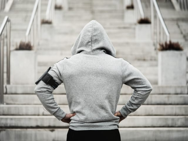 Rear view of a man in a hooded sweatshirt about to run up stairs