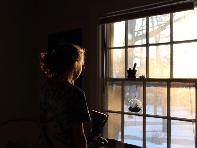 woman looking out the window at snowy scene