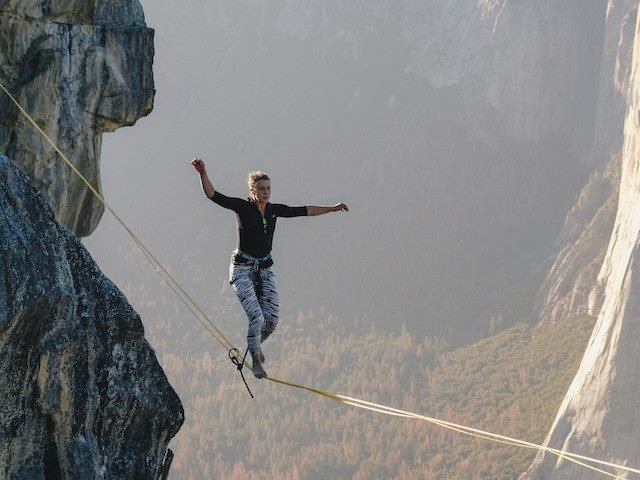 woman walking a tightrope between two mountains