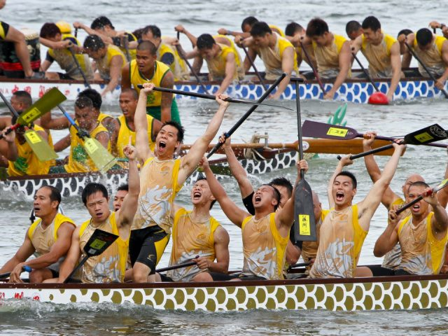 group of rowers celebrate victory in the foreground with other teams in the background