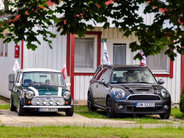 Mini Clubman and classic Austin Mini Cooper retro vehicle parked against the background of a house at the International Mini Meeting 2012 in Hungary.