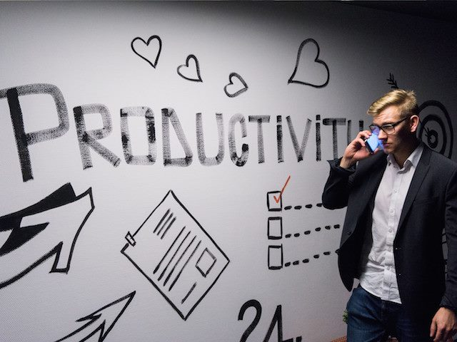 "man on phone in front of ""productivity"" sign"