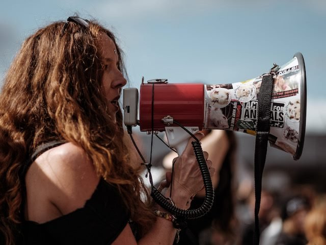 woman with a bullhorn speaking at a protest in London