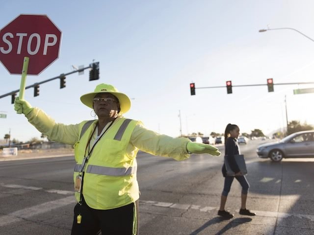 crossing guard stopping traffic with a Stop sign to allow a student to cross safely