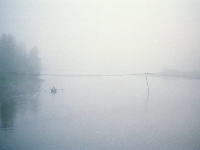 person rowing a boat on a  lake in the mist