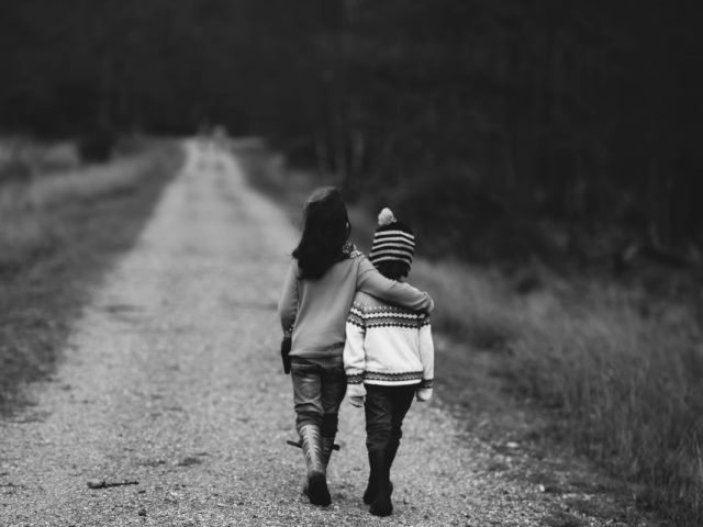 two kids walking down a path with arms around each other