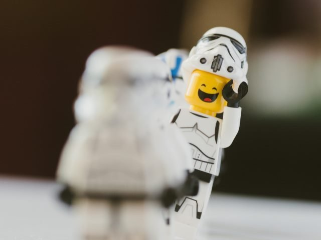 lego minifigure dressed as a stormtrooper smiling at another stormtrooper in the foreground