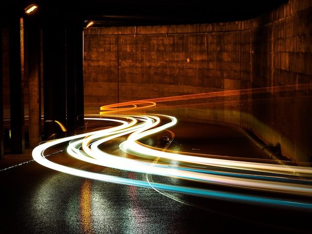 speeding car lights going through a curved tunnel