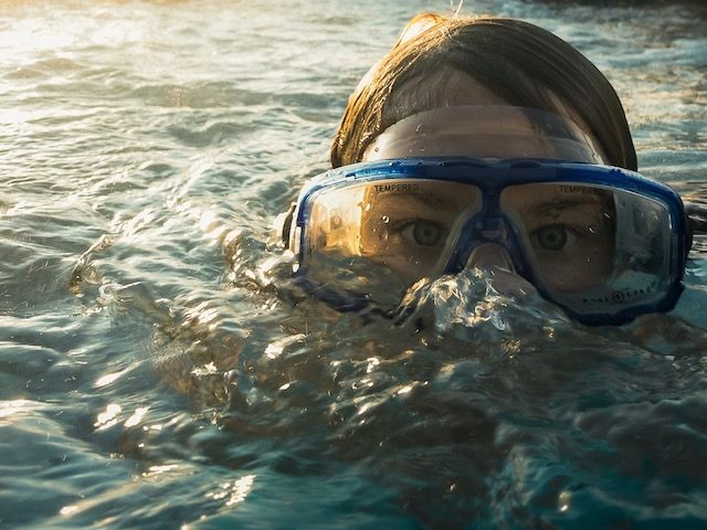 underwater swimmer peeking up with goggles on