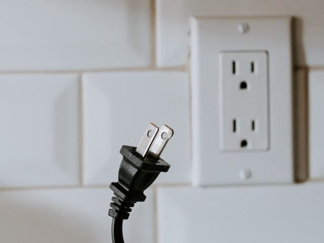unplugged cord in front of electric wall outlet