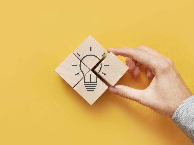 light bulb image made out of wooden blocks on a yellow background