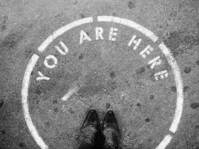 "shoes in a circle on pavement with writing stating ""you are here"""