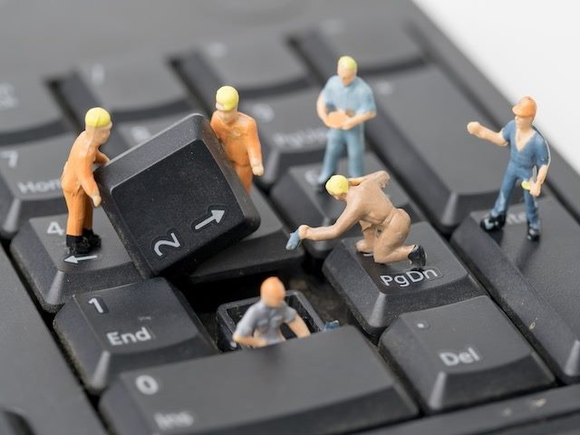 miniature figurines working on a computer keyboard