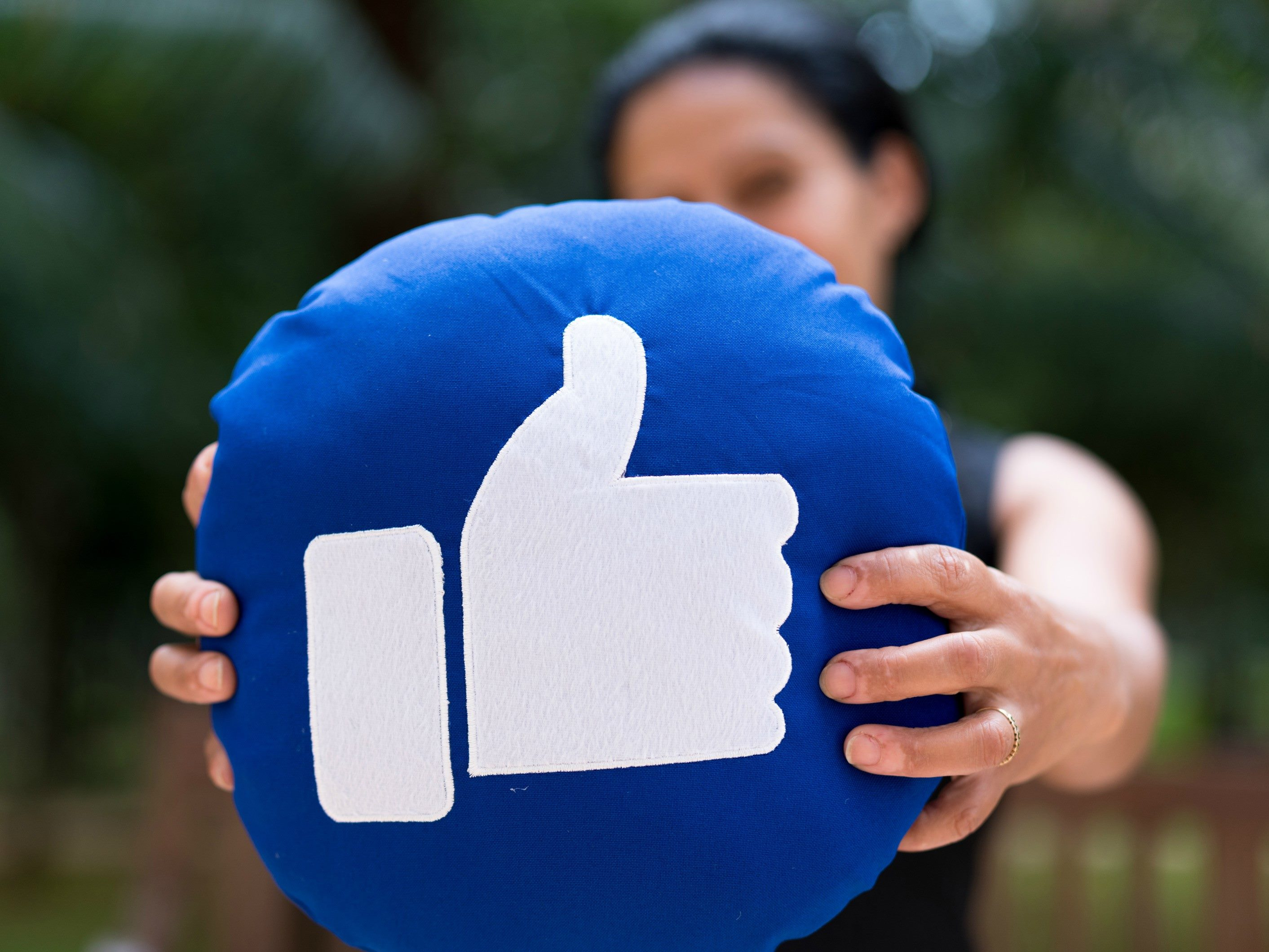 "A woman holding up a pillow with the Facebook ""like"" icon on it."